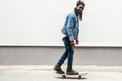 African guy in jeans with dreadlocks rides a skateboard on the sidewalk against a white wall. Street urban sport