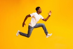 African guy jump, run fast, hurry up to sales or discounts, wear casual style clothes sneakers on yellow color background