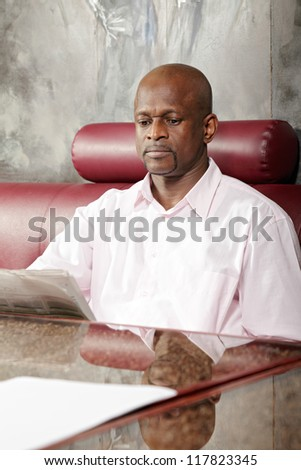 African guy reading newspaper while sitting at table on red leather sofa