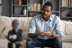 African guy sitting on couch filming online training webinar using camcorder dslr modern professional device camera. Influencer recording advertisement feedback for client, makes job interview concept