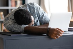 African guy student fall asleep on desk due to long time study prepare for university exams. Overworked employee sleeps at workplace table near opened laptop, fatigue need rest, lack of energy concept
