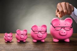 African Hand Putting Coin In Piggybank. Pension Money Fund