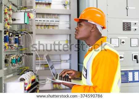 african industrial electrician working in power plant control panel