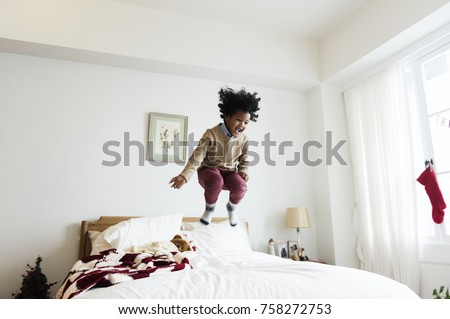 African kid having a fun time jumping on a bed