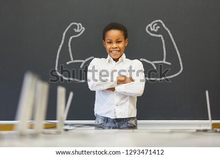 African kid in front of blackboard with muscles