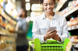 African Lady Customer Doing Grocery Shopping Using Smartphone Walking With Cart In Supermarket. Selective Focus. Woman Using Groceries Shopping Application On Phone Bying Food In Super Market