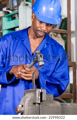 african machinist hammering on metal material
