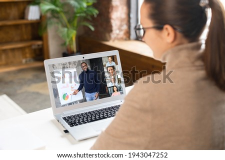 African male teacher, online tutor or business coach is conducting webinars, training, video classes on the laptop screen, a young woman is watching, other people involved. E-learning, online meeting