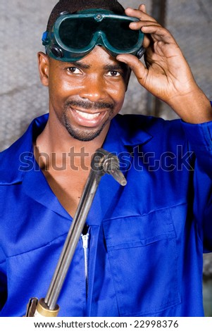 african male welder with protective goggles and gas welding machine
