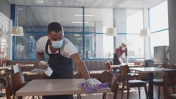 African male worker cleaning table with disinfectant in restaurant during coronavirus outbreak. Waiter in protective mask and gloves disinfecting table with spray and cloth