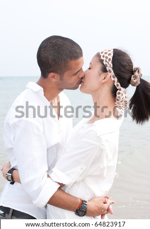 stock photo : african man and asian woman lover on the beach