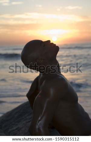 African man at beach during sunset