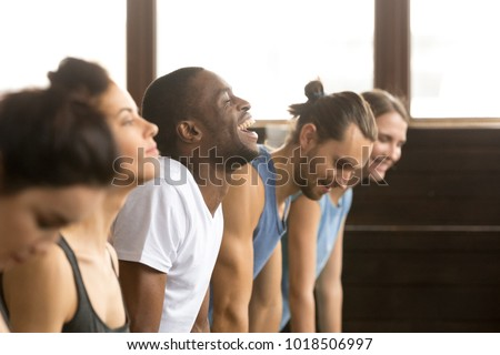 African man beginner laughing having fun trying to do yoga pose, push ups plank or stretching in upward facing dog exercise at group training class with multiracial diverse people, closeup side view