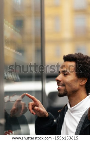 African man buys drink or sweets at vending machine outside. #1556153615