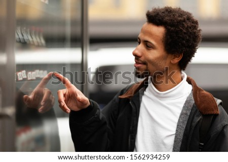 African man buys drink or sweets at vending machine outside. #1562934259