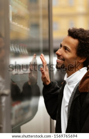 African man buys drink or sweets at vending machine outside. #1569765694