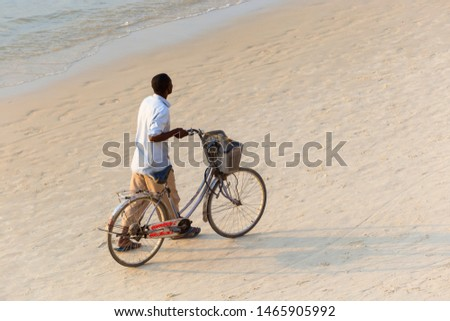 african man casually walking next to his bicycle on a sandy beach viewed from above and behind portraying a relaxed casual scene