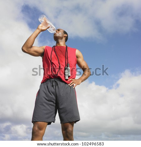 African man drinking from water bottle