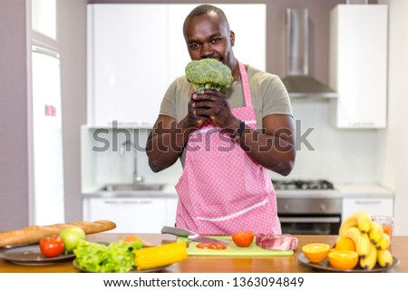 African man eating fresh broccoli in kitchen cooking healthy Breakfast with fresh vegetables