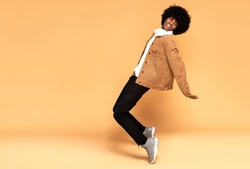 African man having fun during photoshoot in studio, dancing and smiling.