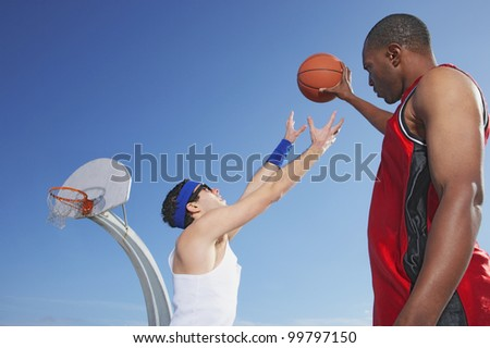 African man holding basketball away from nerd
