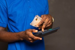african man holding some money and using a calculator