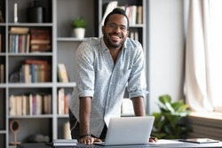 African man in glasses casual shirt leaned over laptop stands in modern office room pose for camera. Company head portrait, career growth development, intelligent worker, application developer concept
