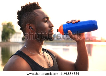 African man in sports clothing drinking water exercise in beach outdoor portrait, at sunset or sunrise. #1198886554