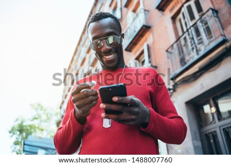 african man listening music through earphones. He's putting the earphone is his ear.