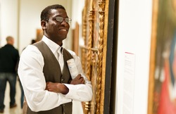 African man looking at exhibit on exposition of historical museum