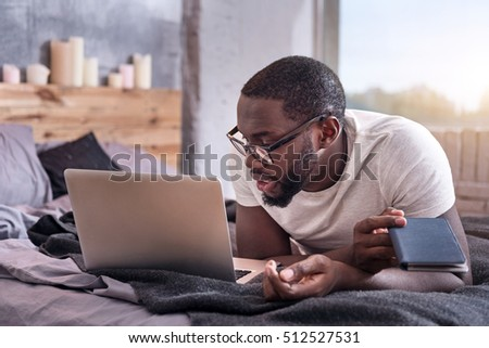 African man looking at his laptop