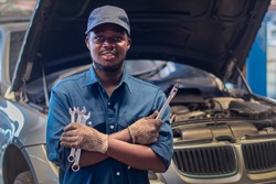 African man mechanic in uniform with crossed arms and wrenches standing at the car repair station