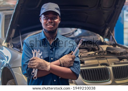 African man mechanic in uniform with crossed arms and wrenches standing at the car repair station Photo stock ©