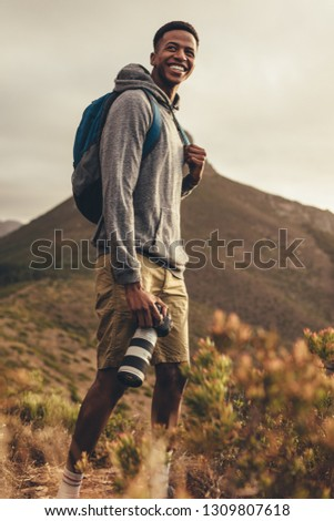 African man on hiking trip with his dslr camera. Smiling photographer hiking in nature for new content for his social media.