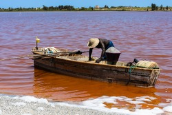 African man on the wooden boat over the Senegal red lake, called Lake Retba or Lac Rose