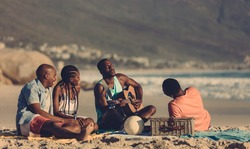 African man playing guitar for friends on the beach. Group of friends having picnic at the seashore.