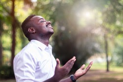 African man praying for thank god with light flare in the green nature