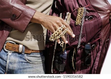 African man selling jewelry inside jacket