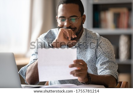 African man sit at desk hold postal correspondence letter read good news feel proud by personal business achievement, got hired, receive reward, financial success statement, approved bank loan concept Stockfoto ©