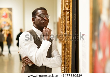 African man standing at hall of Art Museum among exhibits of antiquity
