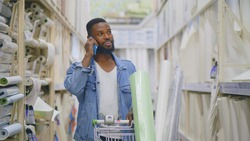 African man talking on phone pushing cart with wallpapers in diy store. Young male consumer buying wallpapers in hardware store for home renovation and redecoration