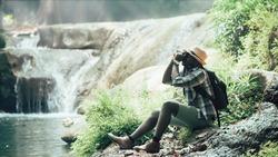 African man traveler take photo at the waterfall.16:9 style