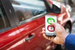 African Man Unlocking Car Using Smartphone App