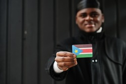 African man wear black durag hold South Sudan flag at hand isolated dark background.