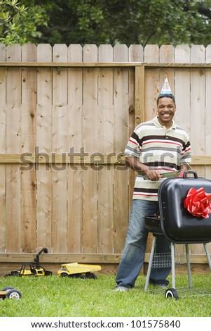 African man wearing party hat and barbequing