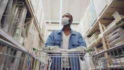 African man wearing protection facemask choosing wallpaper in hardware store. Low angle view of afro guy pushing shopping cart buying materials in house improvement store wear safety mask and gloves