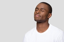 African man wearing white t-shirt closed eyes pose aside isolated on grey blank copy space for creative thoughts advertisement text, guy dreaming feels calmness placidity balance and harmony concept