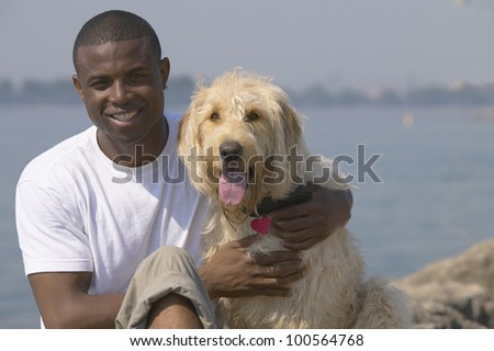 African man with dog at beach
