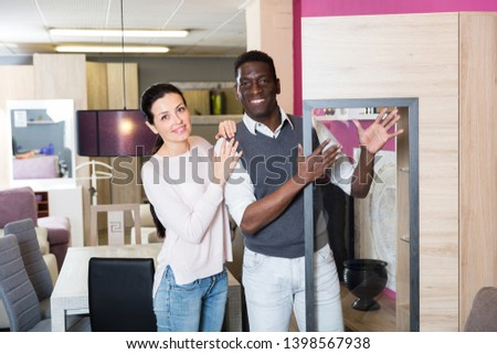 African man with his wife are choosing new cabinet for living room in the store.