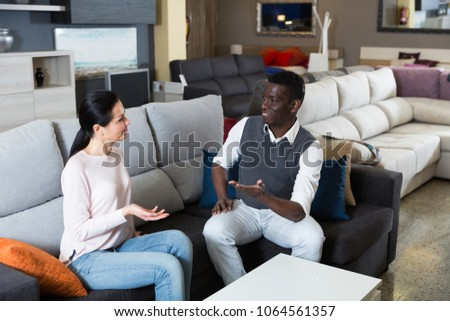 African man with his wife are choosing new furniture for interior their room in the store.